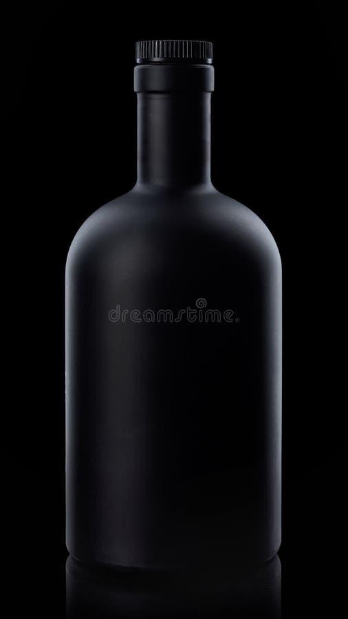 Botella de whisky negra en fondo oscuro imagen de archivo libre de regalías