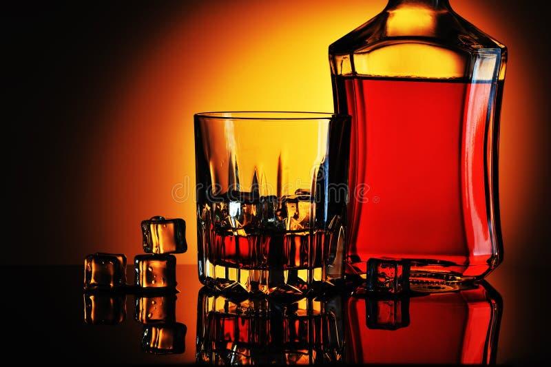 Botella de whisky y de vidrio con hielo fotos de archivo libres de regalías