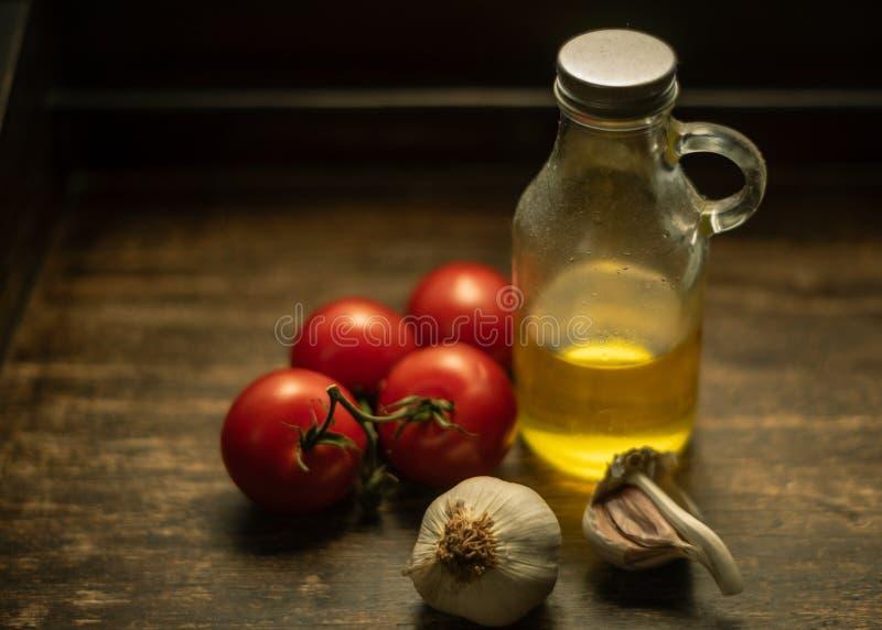 Botella del ajo, del tomate de la vid y de cristal con aceite en fondo de madera del vintage foto de archivo libre de regalías