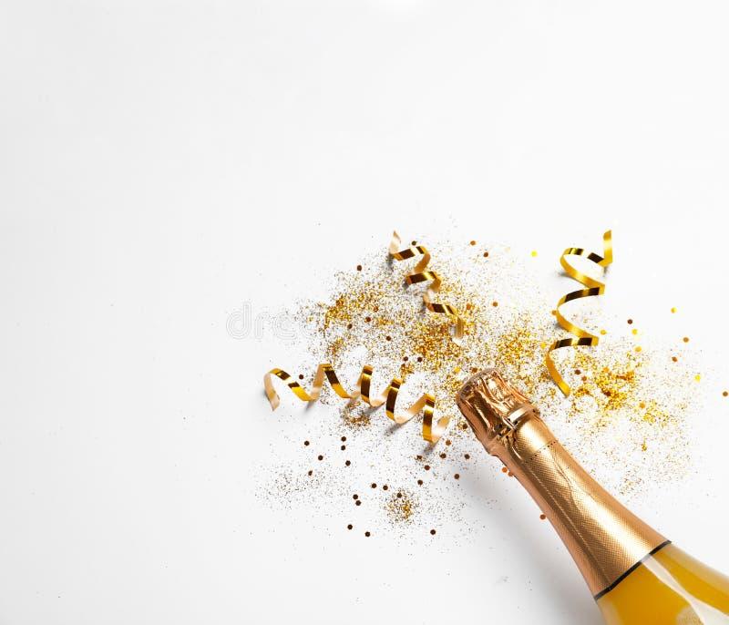 Botella del champán con brillo del oro, confeti en el fondo blanco, visión superior Celebración hilarante imagen de archivo libre de regalías