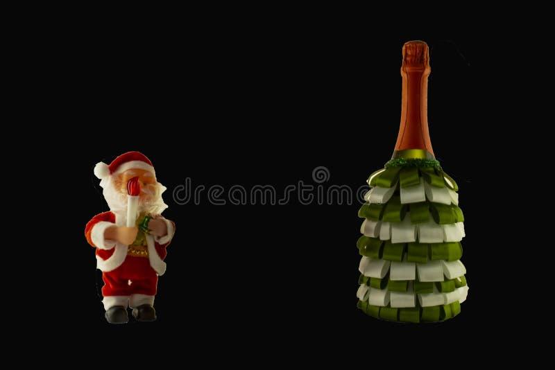 Botella del champán de la decoración de la Navidad con las cintas y Santa Cla imagen de archivo