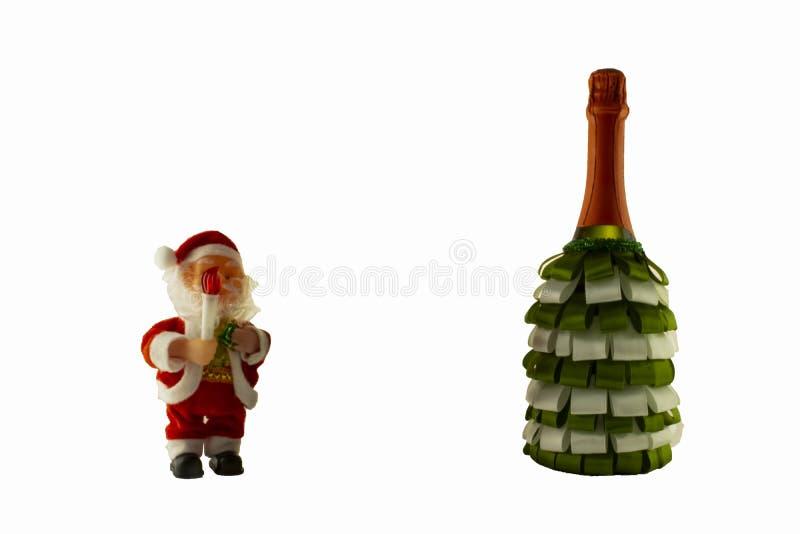 Botella del champán de la decoración de la Navidad con las cintas y Santa Cla fotos de archivo libres de regalías