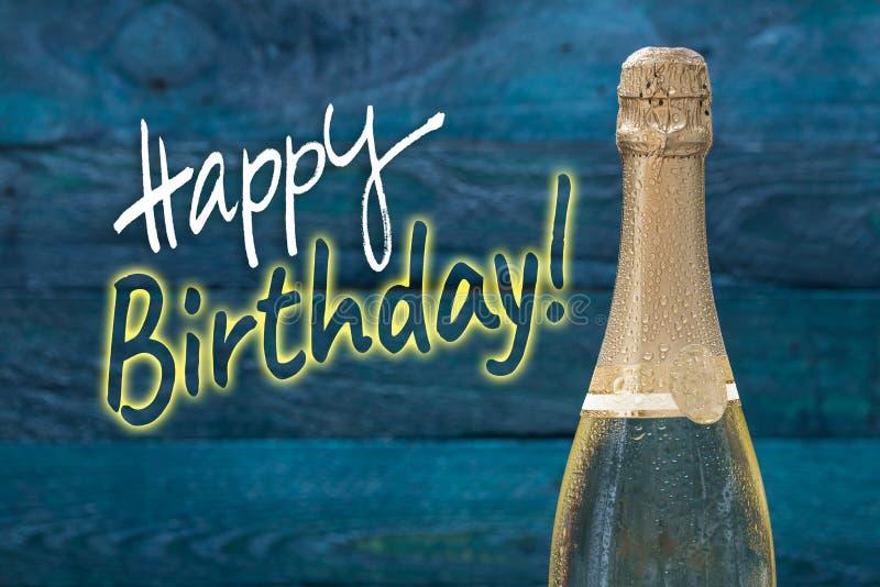 Botella del champán del feliz cumpleaños con descensos del agua contra un PE fotos de archivo libres de regalías