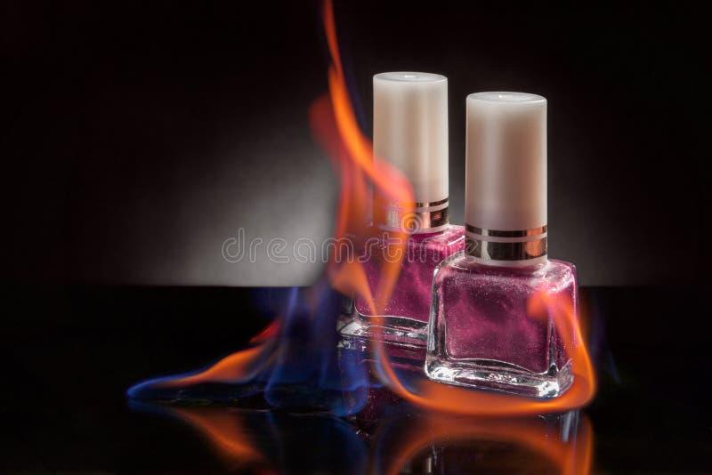 Botella del esmalte de uñas en una llama del fuego en un fondo negro fotografía de archivo libre de regalías
