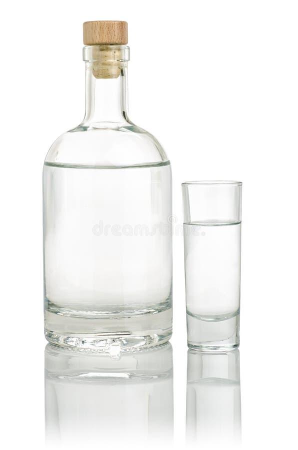 Botella del licor con un vaso de medida lleno fotografía de archivo