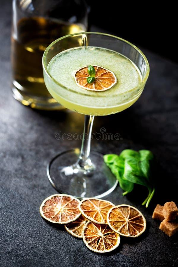 Botella del licor, vidrio de cóctel, azúcar marrón, hojas de la albahaca y rebanadas secadas del limón fotografía de archivo