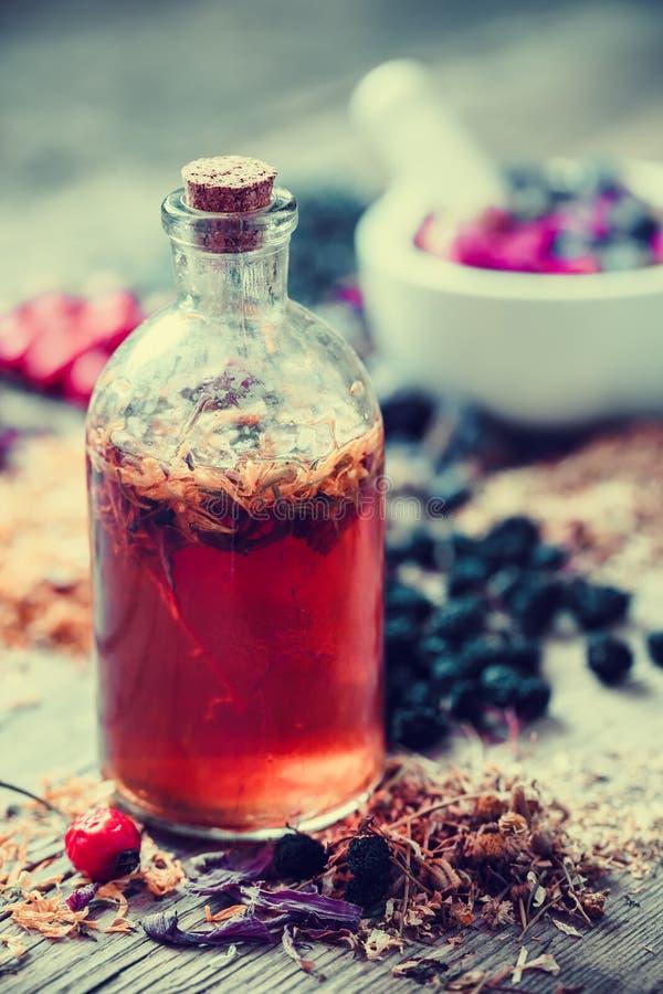 Botella del tinte y mortero de hierbas curativas en fondo foto de archivo
