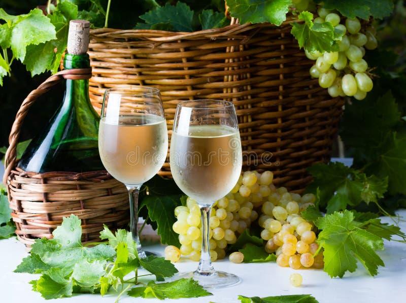 Botella del vino blanco, dos vidrios, manojo de uvas en cesta fotografía de archivo