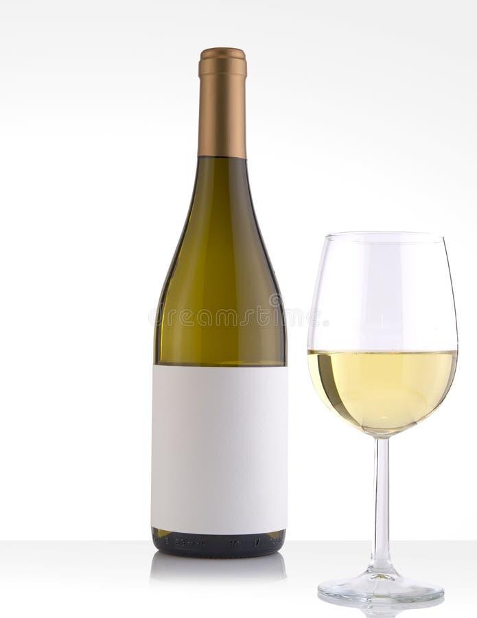 Botella del vino blanco en un fondo y un vidrio blancos imágenes de archivo libres de regalías