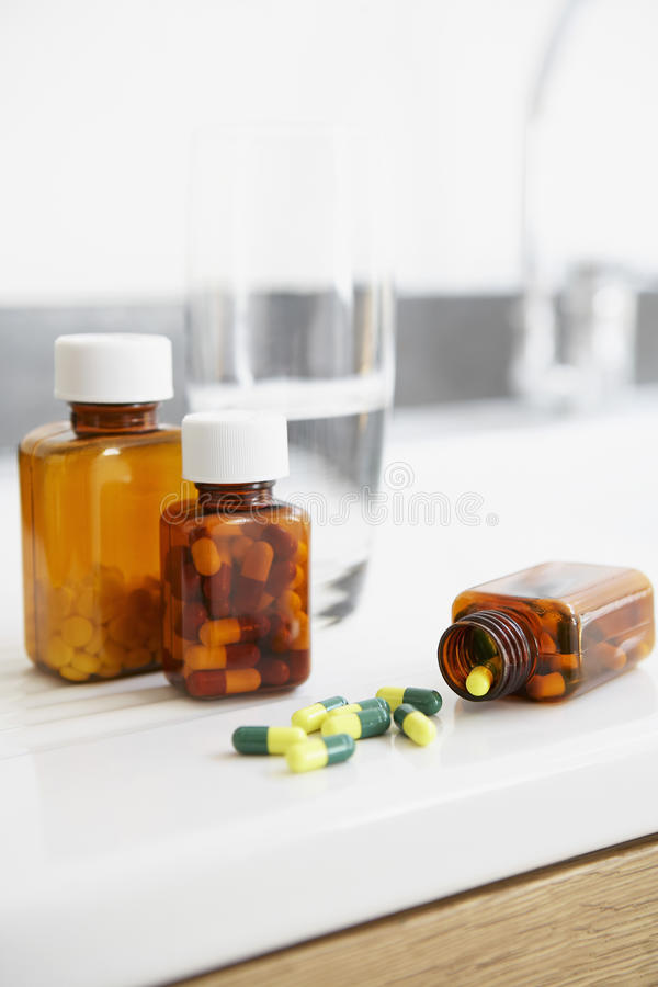 Botella derramada de píldoras en contador en cierre del cuarto de baño para arriba fotos de archivo