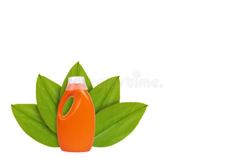 Botella detergente plástica anaranjada en el fondo de hojas verdes Aislado en blanco noción del origen natural fotografía de archivo libre de regalías