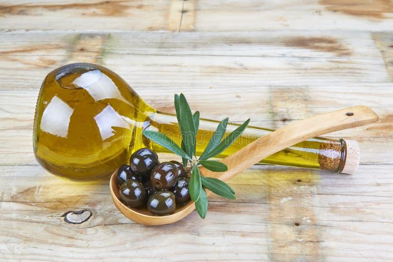 Botella elegante de aceite y de cuchara de oliva con las aceitunas imagenes de archivo