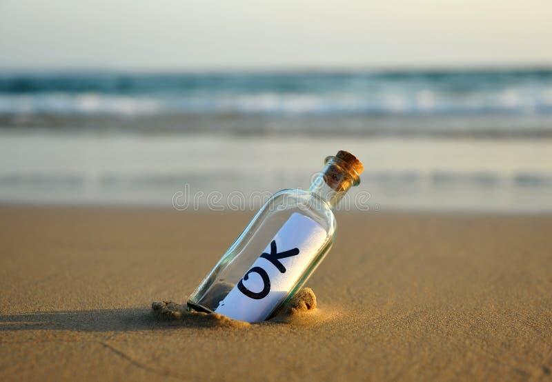 Botella en la playa con una respuesta afirmativa dentro, okey fotografía de archivo libre de regalías