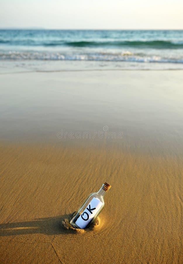 Botella en la playa con una respuesta afirmativa dentro, okey imagen de archivo libre de regalías