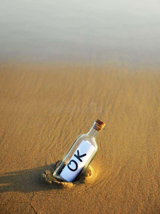 Botella en la playa con una respuesta afirmativa dentro, okey foto de archivo