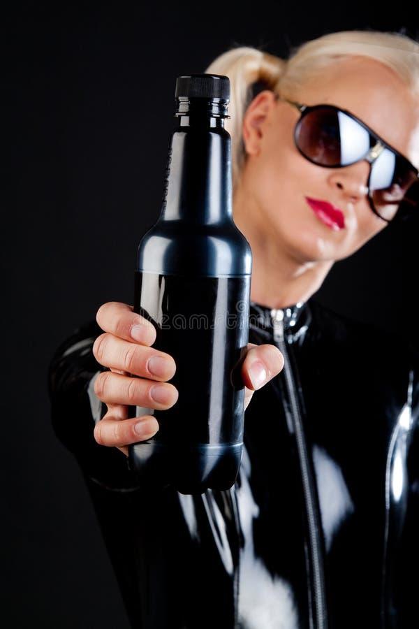 Botella en las manos de la muchacha imagenes de archivo