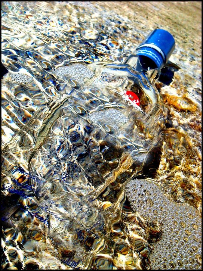 Botella en macro del agua de la playa imagen de archivo