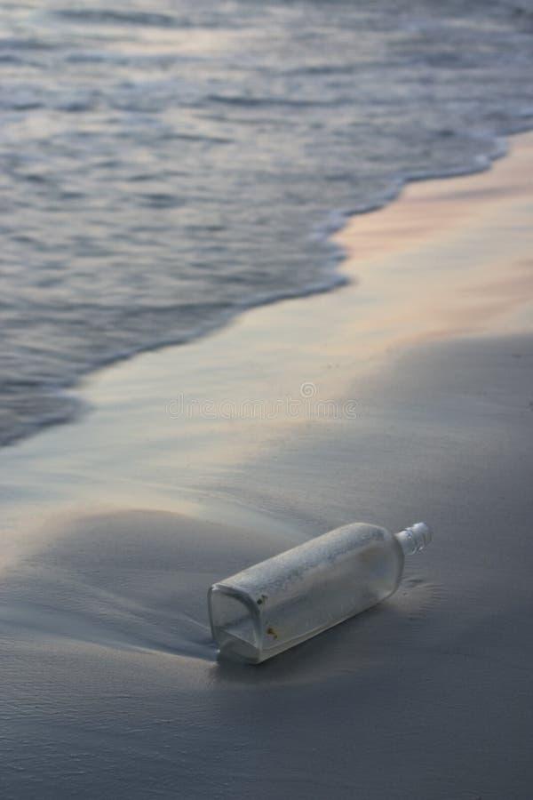 Botella en una playa imagen de archivo
