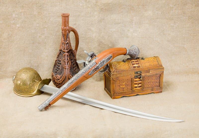 Botella, estoque, espada, pistola y pecho foto de archivo