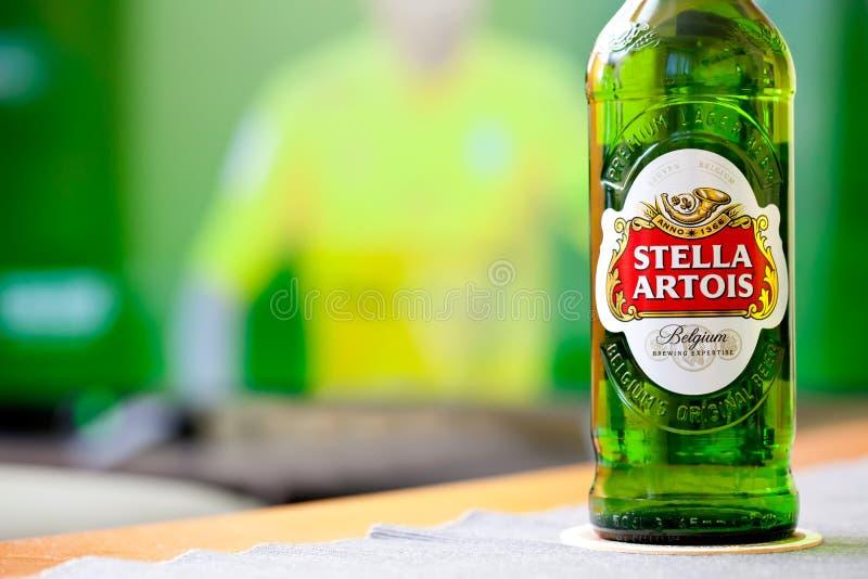 Botella fría de cerveza de Stella Artois en el fondo de la TV, tiempo del socer con el concepto de la cerveza, marca prominente imagen de archivo libre de regalías