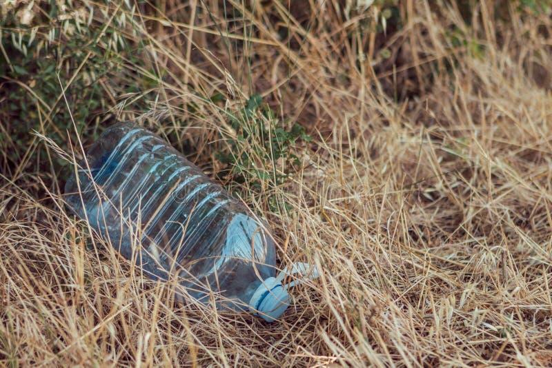 Botella grande de agua entre la hierba en el campo Concepto pl?stico de la contaminaci?n del ambiente fotos de archivo libres de regalías