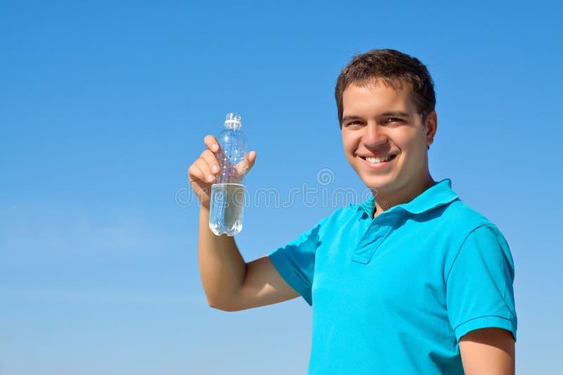 Botella masculina joven de la explotación agrícola de agua fotografía de archivo libre de regalías