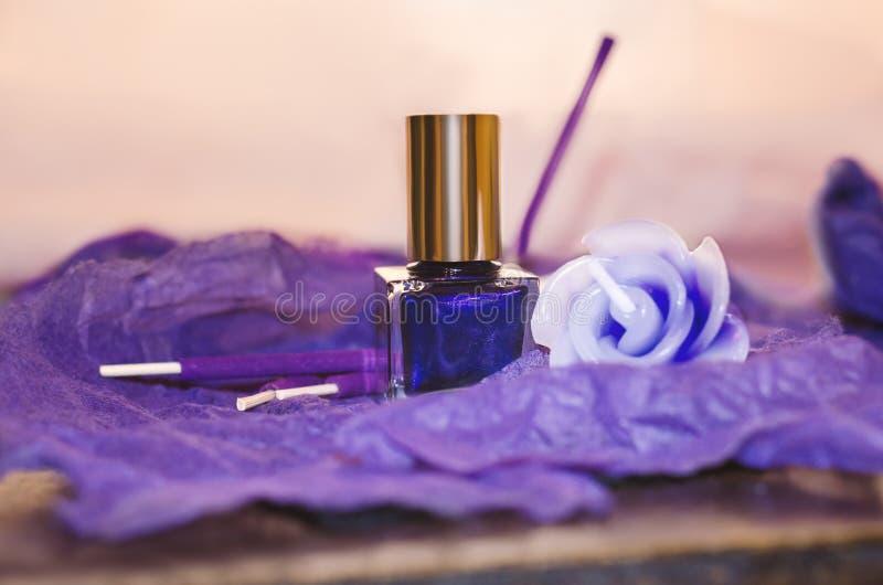 Botella púrpura del esmalte de uñas, vela decorativa e incienso imagen de archivo libre de regalías