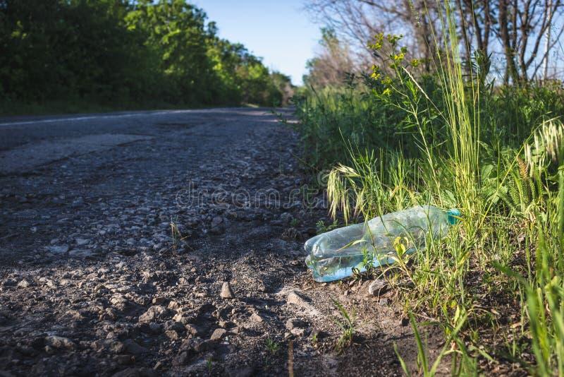 Botella plástica con agua por el camino foto de archivo