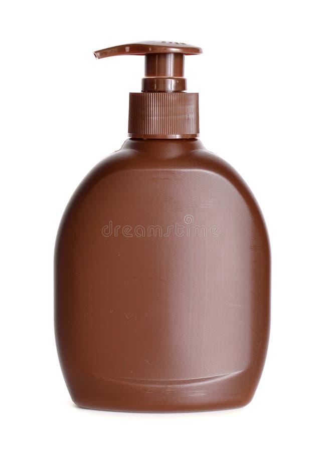 Botella plástica de Brown con el jabón líquido en un fondo blanco fotografía de archivo libre de regalías