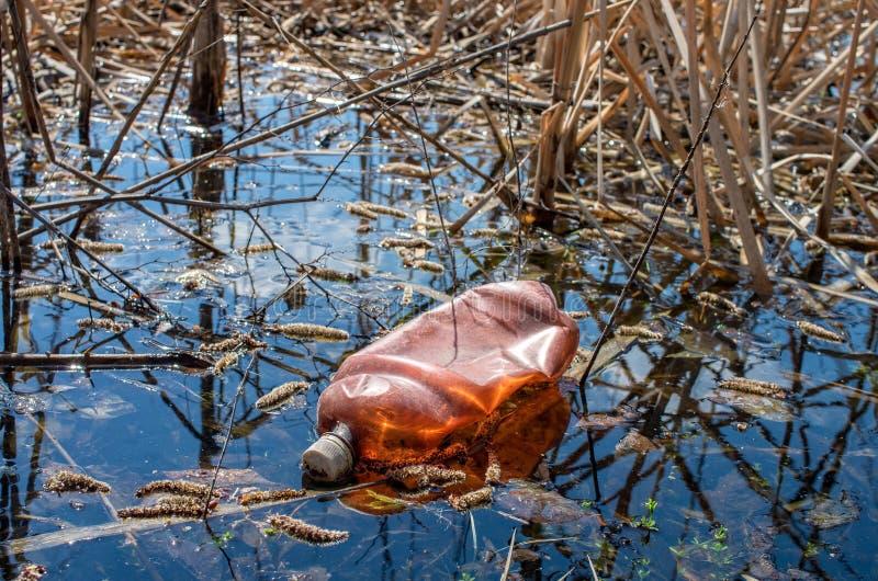 Botella plástica desechada en el río imágenes de archivo libres de regalías
