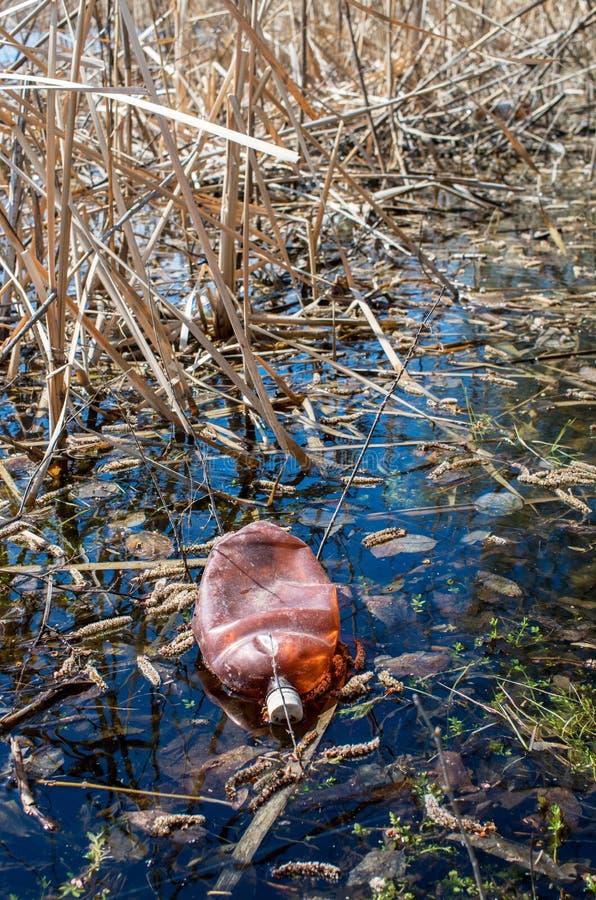 Botella plástica desechada en el río fotos de archivo