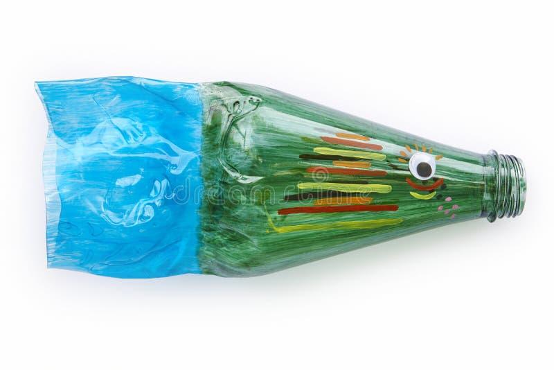 Botella plástica reciclada en una figura de los pescados Basura de la reutilización imagenes de archivo
