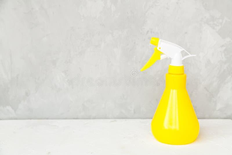 Botella pl?stica amarilla simple del espray de la mano en fondo gris imágenes de archivo libres de regalías