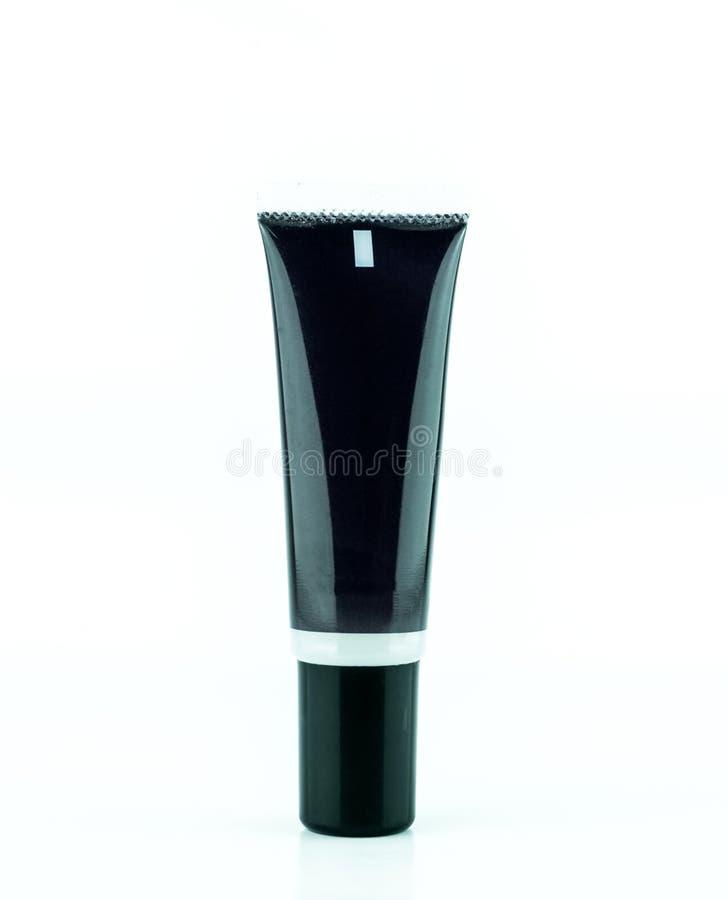 Botella poner crema negra en blanco del tubo o del cosmético aislada en el fondo blanco imagenes de archivo