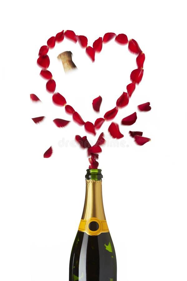 Botella roja en forma de corazón del champán de los pétalos color de rosa foto de archivo