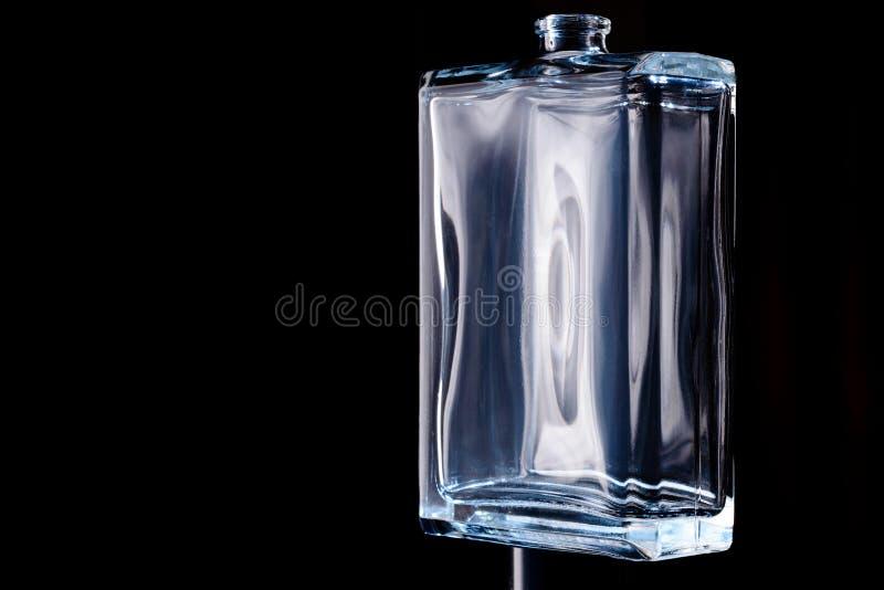 Botella transparente rectangular de cologne aislada en un fondo negro imágenes de archivo libres de regalías