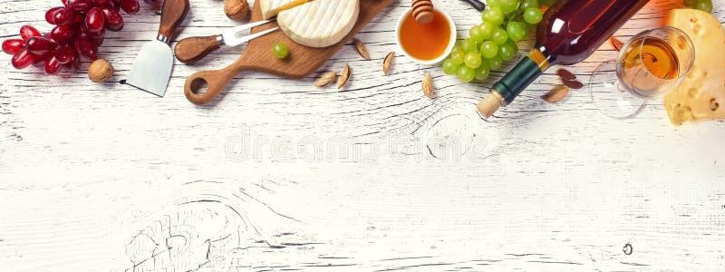Botella, uva, miel, queso y copa del vino blanco en el tablero de madera blanco imagen de archivo