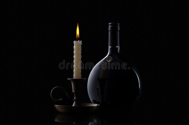 Botella, vela y vidrio de vino en fondo negro imagen de archivo