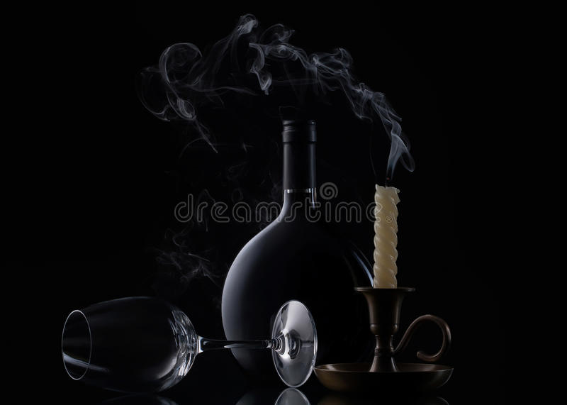 Botella, vela y vidrio de vino en fondo negro fotos de archivo libres de regalías