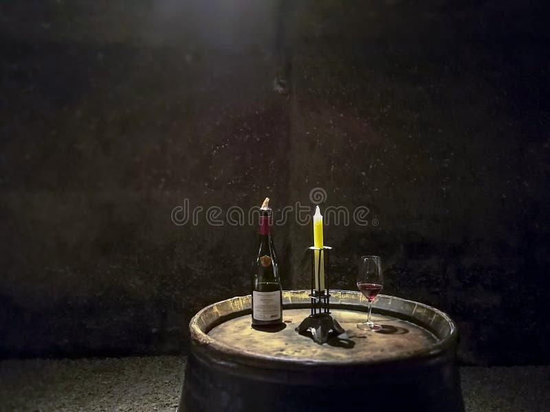 Botella, vela y vidrio descansando sobre un barril de vino fotos de archivo libres de regalías