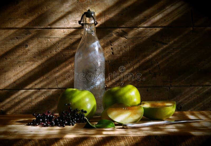 Botella vieja con las manzanas verdes fotos de archivo libres de regalías