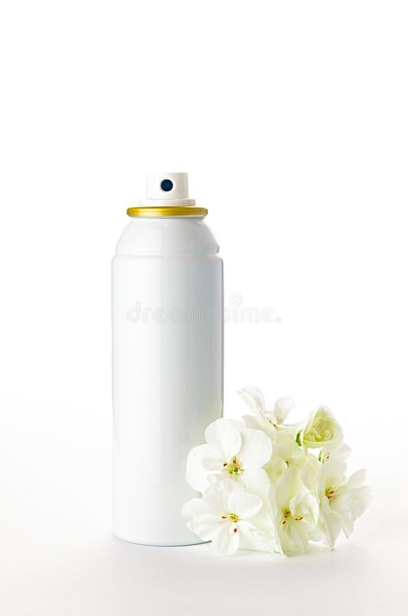 Botella y flores metálicas del espray en el fondo blanco foto de archivo