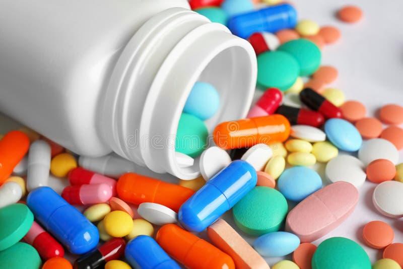 Botella y muchas píldoras coloridas foto de archivo libre de regalías