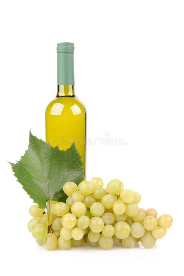 Botella y uvas del vino blanco foto de archivo