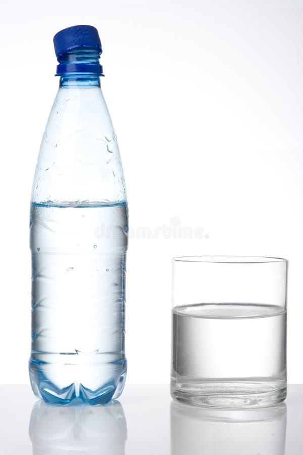 Botella y vidrio con agua imagen de archivo libre de regalías