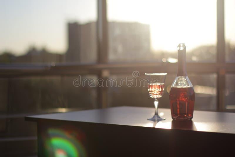 Botella y vidrio con el vino en la tabla en oficina fotos de archivo
