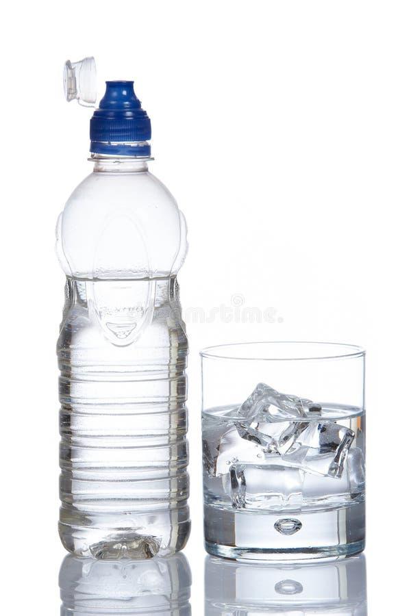 Botella y vidrio de agua mineral con las gotitas imagen de archivo libre de regalías