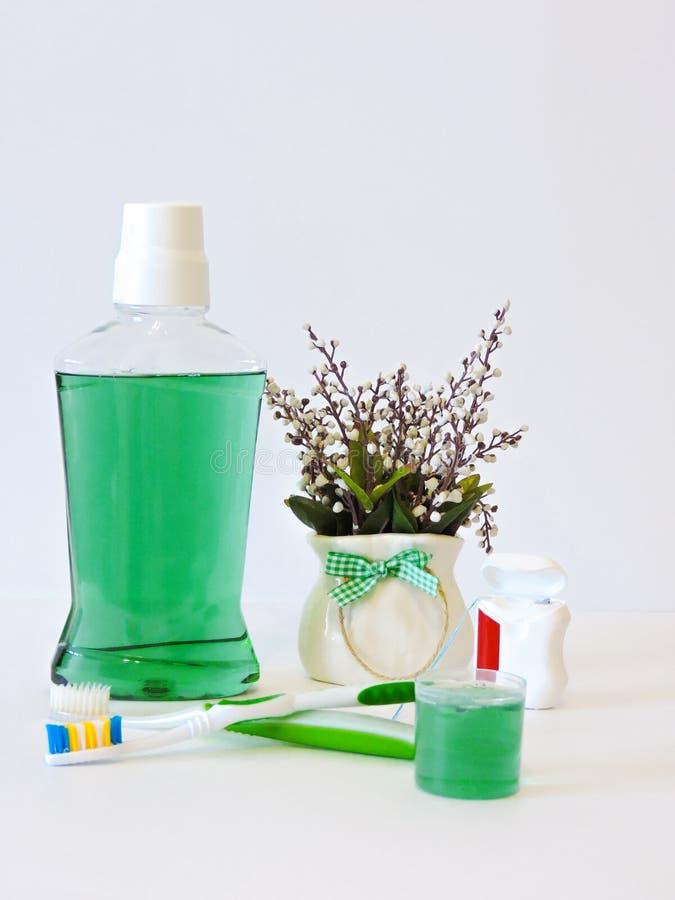 Botella y vidrio de enjuague en estante del baño con el cepillo de dientes Concepto dental de la higiene oral Sistema de producto fotografía de archivo