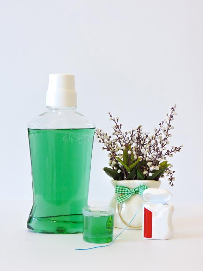 Botella y vidrio de enjuague en estante del baño con el cepillo de dientes Concepto dental de la higiene oral Sistema de producto fotos de archivo libres de regalías