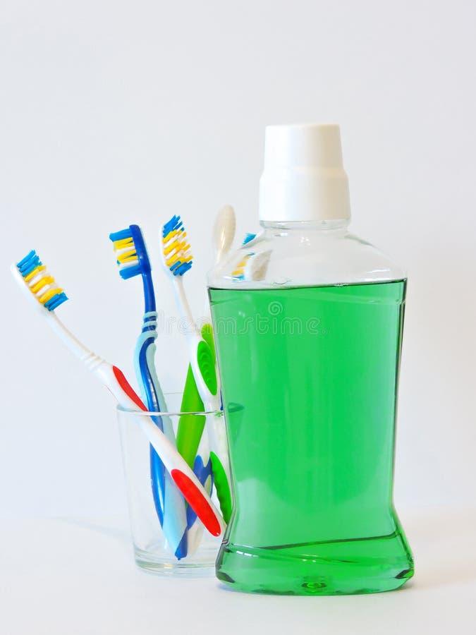 Botella y vidrio de enjuague en estante del baño con el cepillo de dientes Concepto dental de la higiene oral Sistema de producto fotografía de archivo libre de regalías